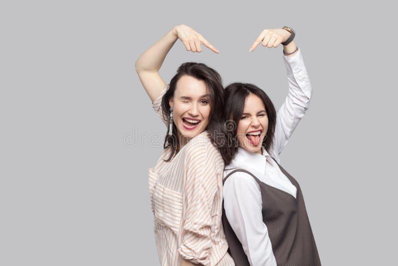 Portret van grappige mooie donkerbruine beste vrienden in toevallige stijl status rijtjes en het richten van elkaar met grappig g stock foto