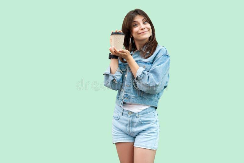 Portret van grappige mooie jonge donkerbruine vrouw in toevallige denimstijl die en beschikbare kop van hete drank bevinden zich  stock foto