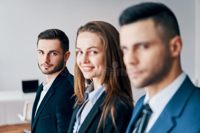Portret van groep jonge bedrijfsmensen op een rij in bureau royalty-vrije stock fotografie