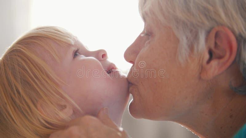 Portret van grootmoeder en kleindochter Oma die haar kleindochter kust royalty-vrije stock foto's