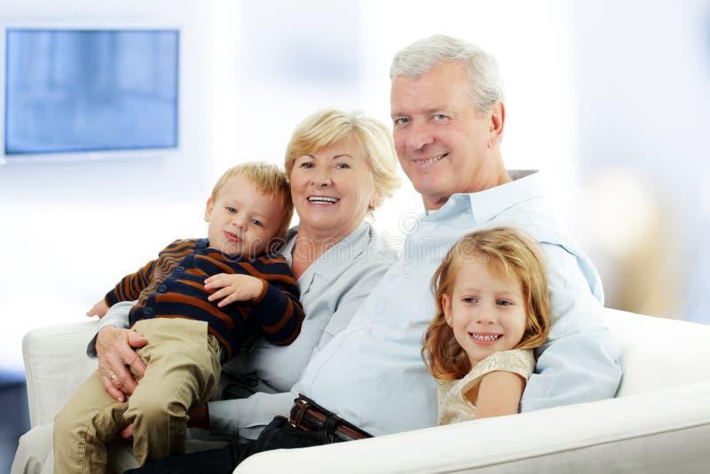 Portret van Grootouders met Kleinkinderen die samen ontspannen royalty-vrije stock foto's