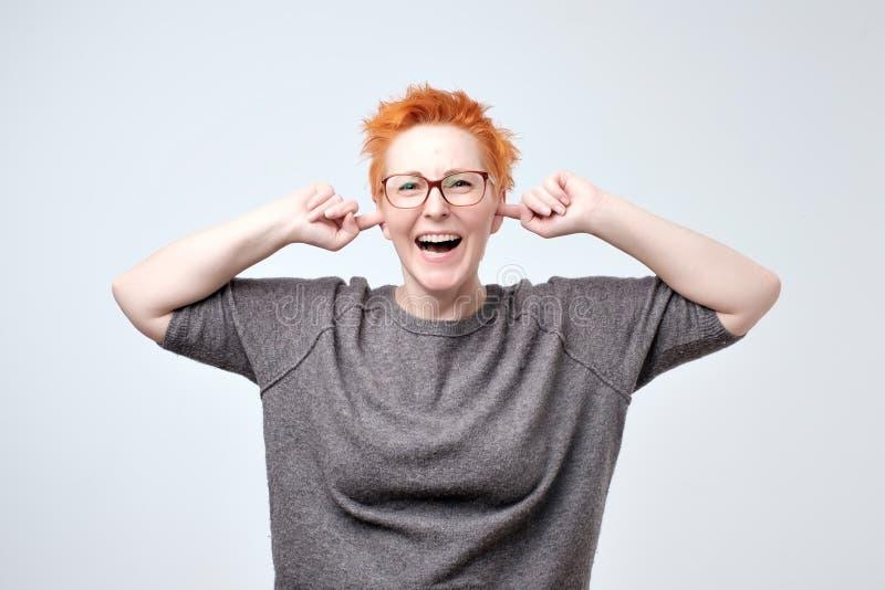 Portret van heldere rijpe caucasainvrouw met rood haar die oren behandelen met handen stock afbeeldingen