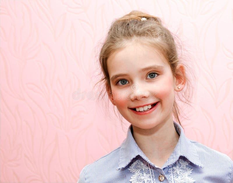 Portret van het aanbiddelijke glimlachende geïsoleerde kind van het meisjeschoolmeisje stock foto