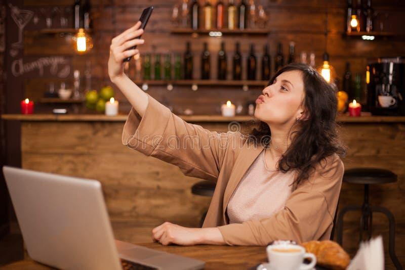 Portret van het aantrekkelijke jonge Kaukasische meisje nemen selfie in een toevallige koffiewinkel stock afbeelding