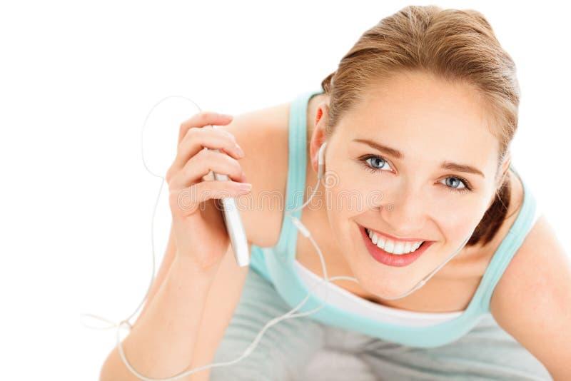 Portret van het aantrekkelijke jonge vrouw luisteren aan muziek bij gymnastiek stock fotografie