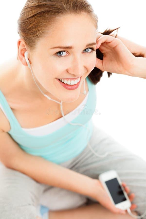 Portret van het aantrekkelijke jonge vrouw luisteren aan muziek bij gymnastiek royalty-vrije stock foto's