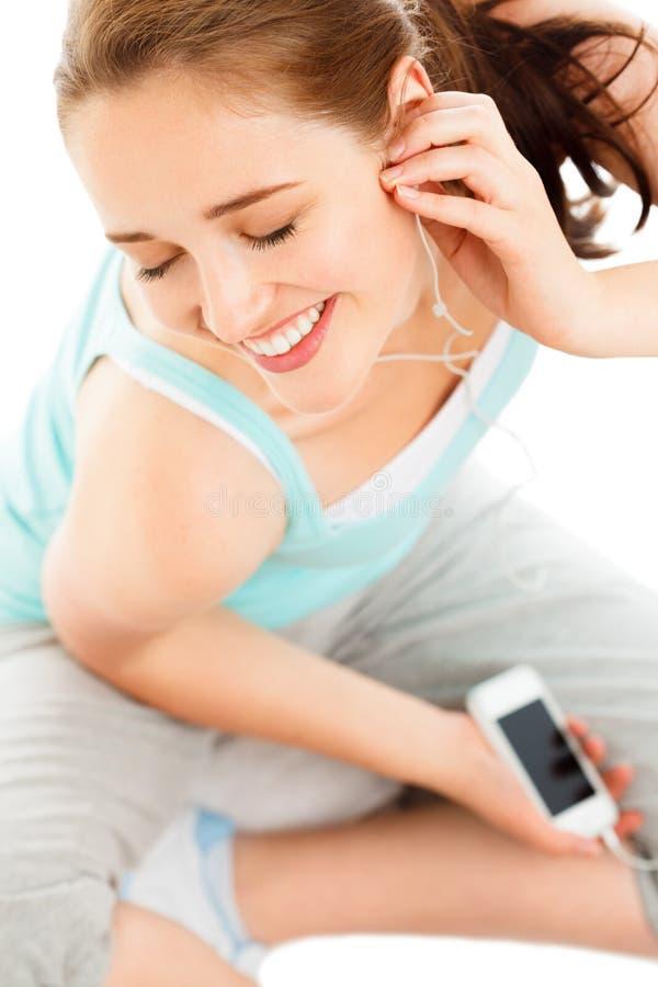 Portret van het aantrekkelijke jonge vrouw luisteren aan muziek bij gymnastiek stock foto