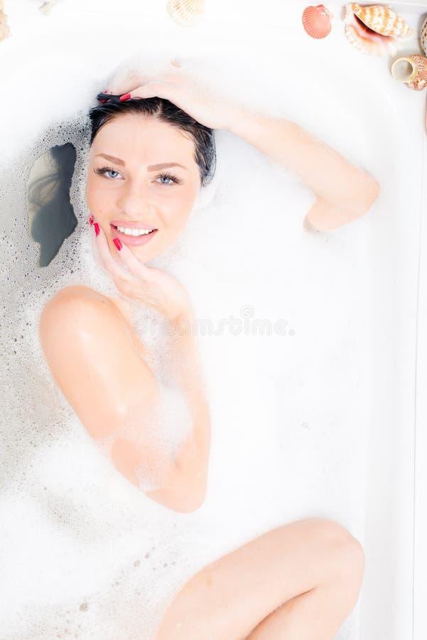 Portret van het aantrekkelijke mooie sexy blauwe ogen jonge vrouw liggende ontspannen in het luxebad met schuim het gelukkige gli royalty-vrije stock foto's