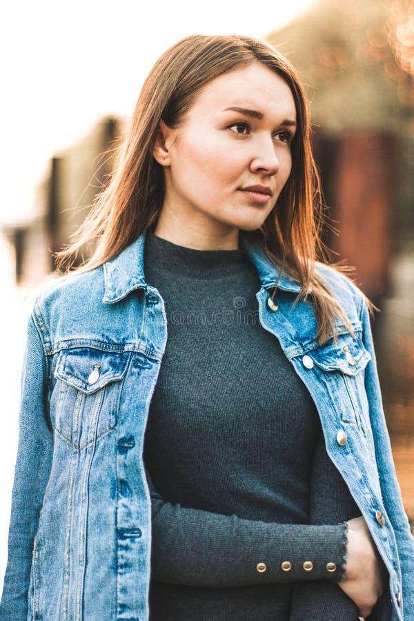 Portret van het aantrekkelijke, slanke, mooie jonge Kaukasische blondemeisje in een jeansjasje Het glimlachende meisje geniet van stock afbeelding