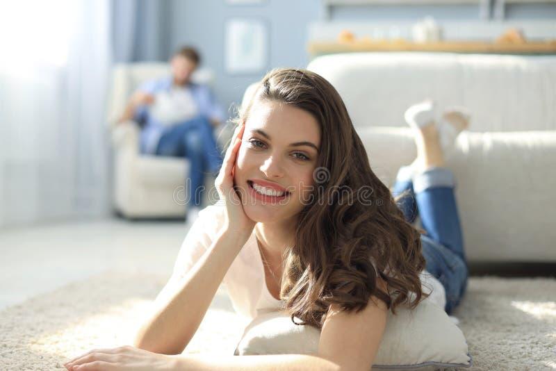 Portret van het aantrekkelijke vrouw ontspannen op vloer met de vage mens op achtergrond royalty-vrije stock foto's