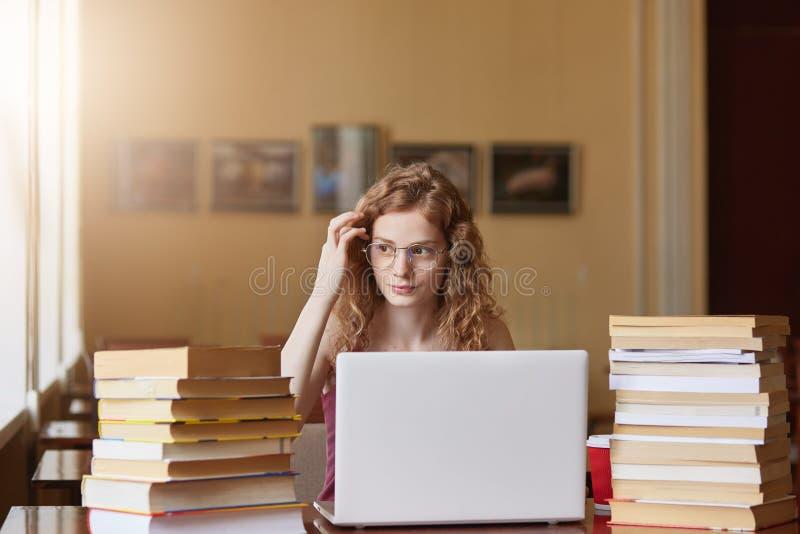 Portret van het aantrekkelijke zoete vrouwelijke opzij bekijken, wat betreft haar haar, die bureau in klaslokaal met stapel van b stock afbeeldingen