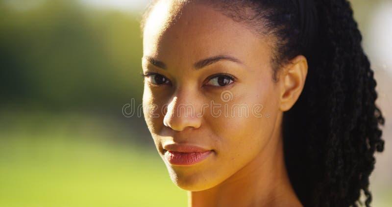 Portret van het Afrikaanse vrouw glimlachen in een park stock afbeeldingen