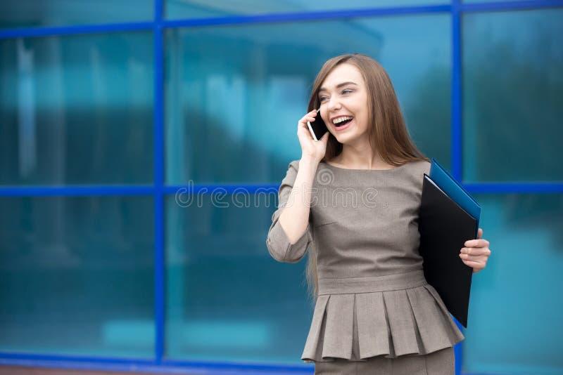 Portret van het bedrijfsvrouw lachen terwijl het spreken op mobiele phon royalty-vrije stock afbeelding