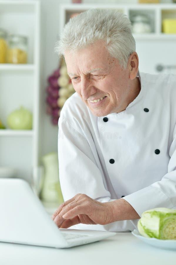 Portret van het bejaarde mannelijke chef-kok koken bij lijst met laptop stock foto