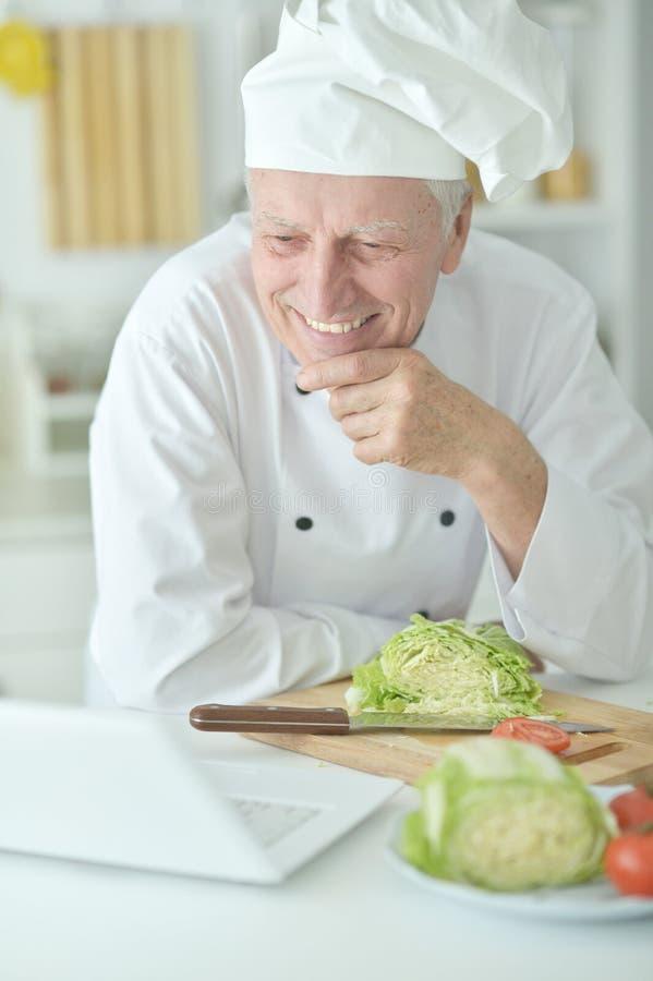 Portret van het bejaarde mannelijke chef-kok koken bij lijst met laptop stock foto's