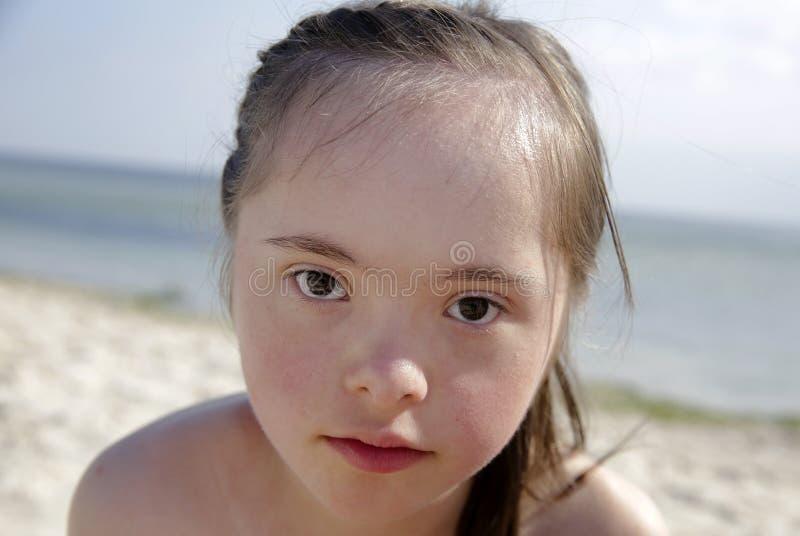 Portret van het benedensyndroommeisje glimlachen op achtergrond van seaÑŽ stock foto