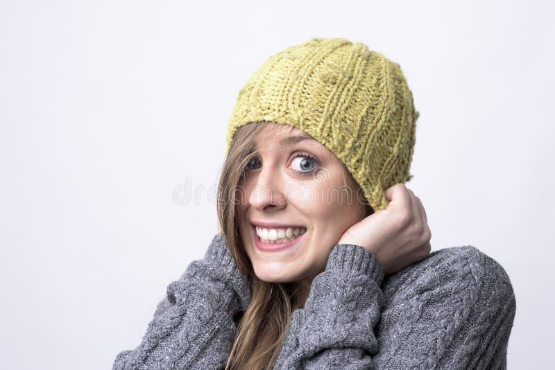 Portret van het bevriezen jonge vrouw met gele beanie die hoofd op koud de winterweer behandelen stock foto's