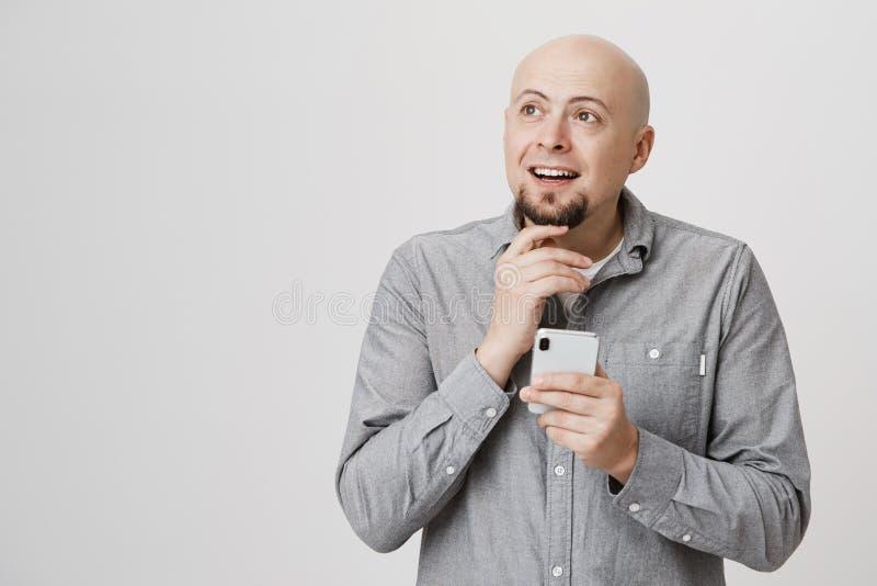 Portret van het charmeren van de kale Kaukasische volwassen mens wat betreft baard terwijl het houden van smartphone en het kijke stock foto's