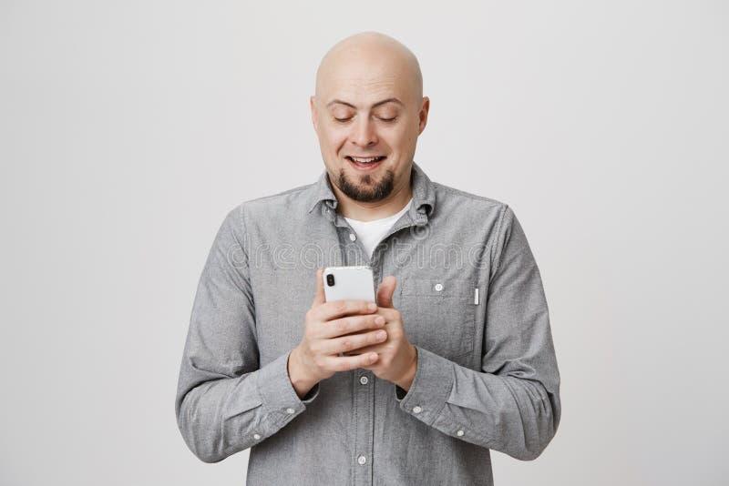 Portret van het charmeren kale Kaukasische smartphone van de kerelholding terwijl overseinen of het doorbladeren, het exprassing  stock foto