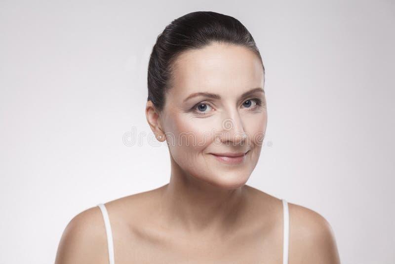 Portret van het charmeren, mooie, aantrekkelijke vrouw met perfecte huid na room, balsem, masker, lotion, die op grijze achtergro royalty-vrije stock fotografie