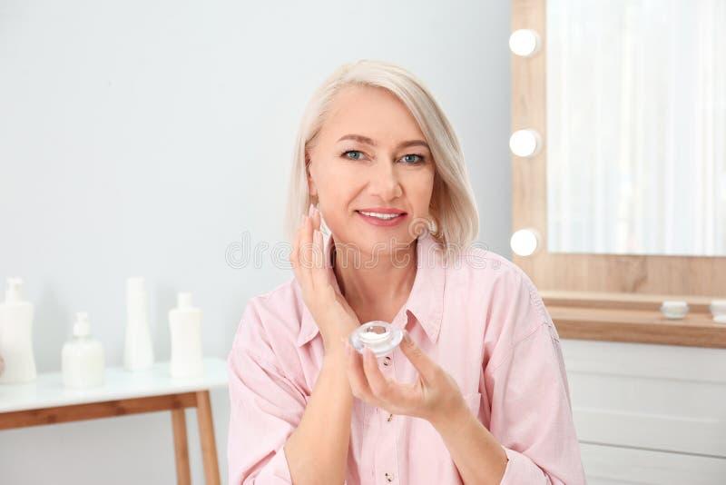 Portret van het charmeren van rijpe vrouw die met gezonde mooie gezichtshuid en natuurlijke make-up room toepassen stock fotografie