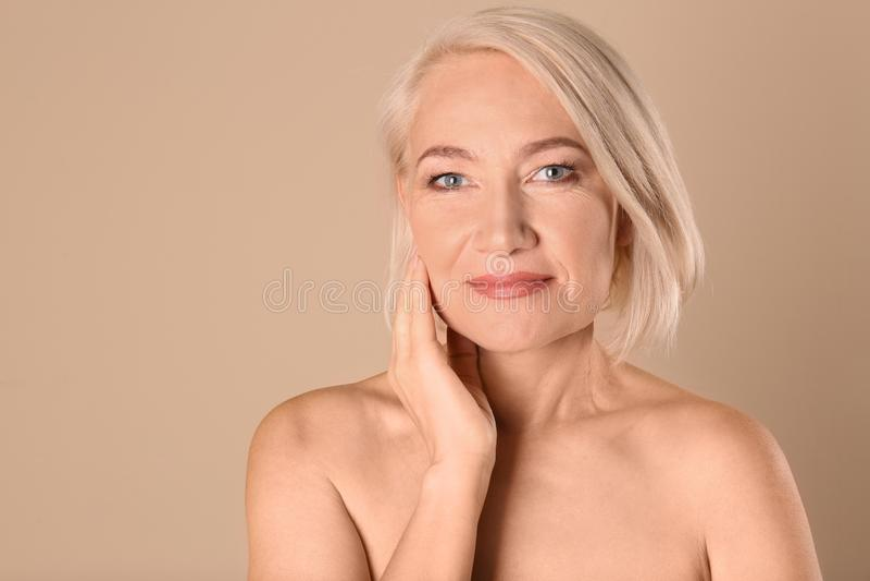 Portret van het charmeren van rijpe vrouw met gezonde mooie gezichtshuid en natuurlijke make-up op beige achtergrond stock foto's