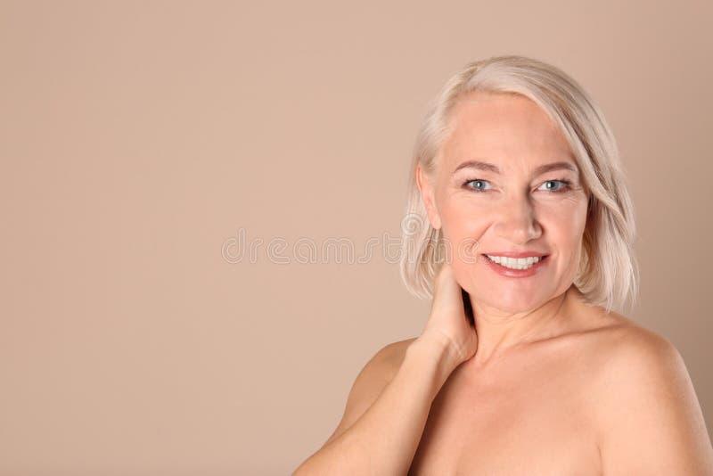Portret van het charmeren van rijpe vrouw met gezonde mooie gezichtshuid en natuurlijke make-up op beige achtergrond royalty-vrije stock afbeelding