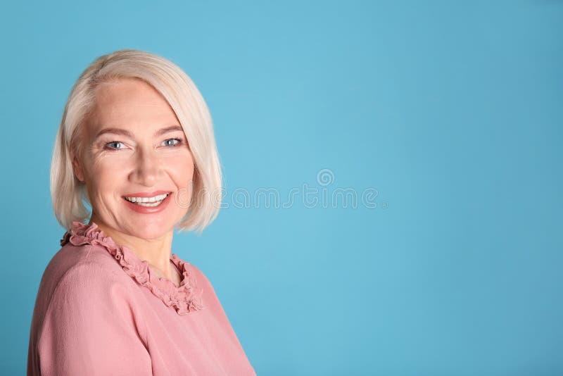 Portret van het charmeren van rijpe vrouw met gezonde mooie gezichtshuid en natuurlijke make-up op blauwe achtergrond stock foto