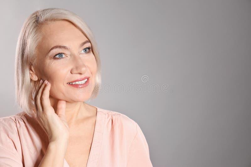 Portret van het charmeren van rijpe vrouw met gezonde mooie gezichtshuid en natuurlijke make-up op grijze achtergrond royalty-vrije stock afbeelding