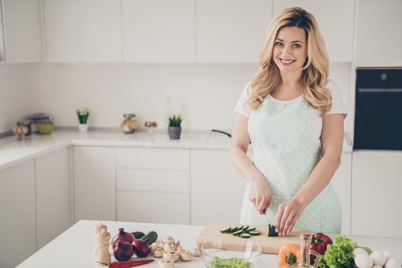 Portret van het charmeren van vrouw met golvend krullend haar die veggie groente van het avondmaalknipsel in keuken maken royalty-vrije stock afbeeldingen