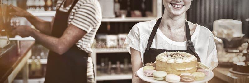 Portret van het dessert van de serveersterholding op caketribune stock foto's