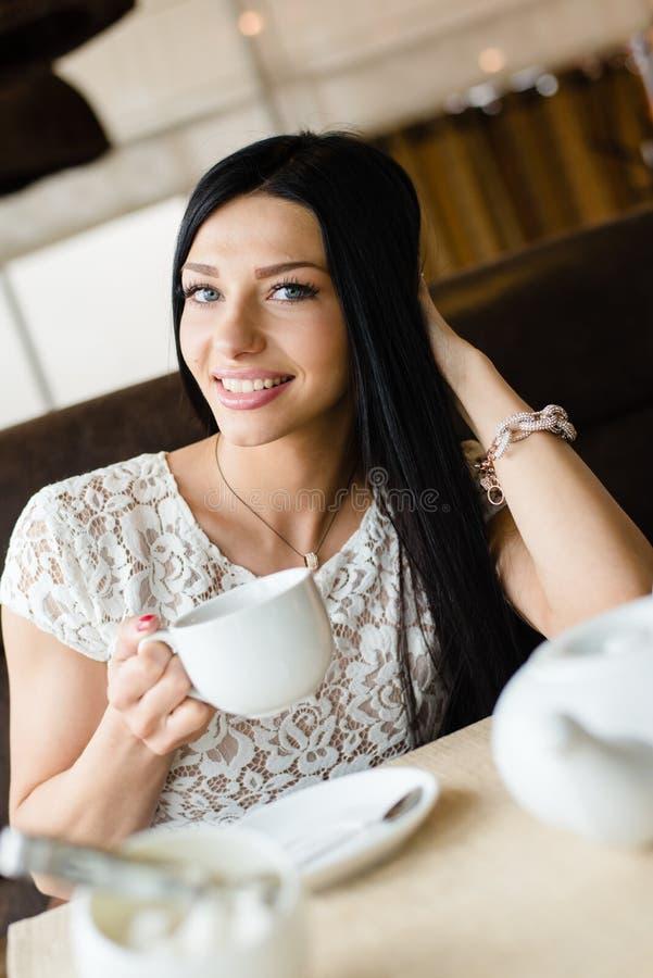 Portret van het drinken van koffie of thee mooie sexy donkerbruin meisjes jonge vrouw die pret hebben die zacht en camera glimlac stock afbeeldingen