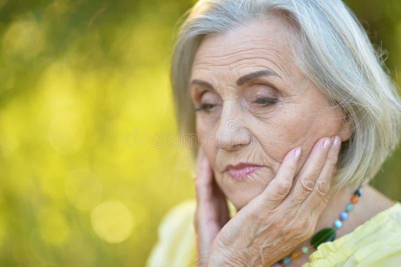 Portret van het droevige hogere mooie vrouw stellen in de lentepark royalty-vrije stock afbeelding