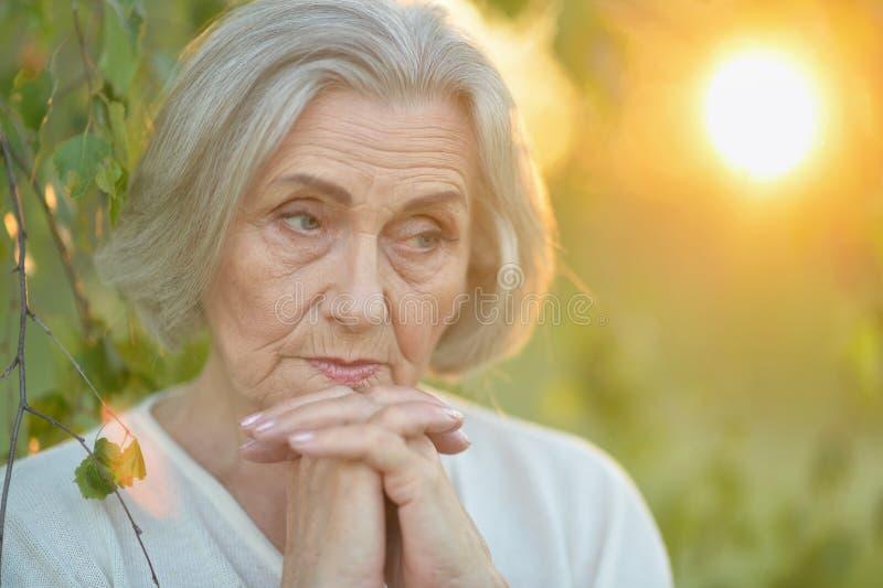 Portret van het droevige hogere mooie vrouw stellen in de lentepark royalty-vrije stock foto's