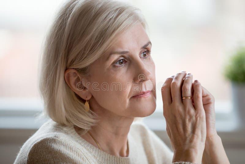 Portret van het droevige vrouw cogitating die thuis alleen zitten royalty-vrije stock fotografie