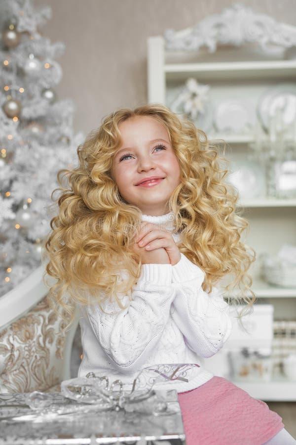 Portret van het dromen van blondemeisje in Kerstmis verfraaide studio stock fotografie
