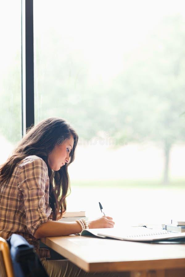 Portret van het ernstige jonge student schrijven stock foto