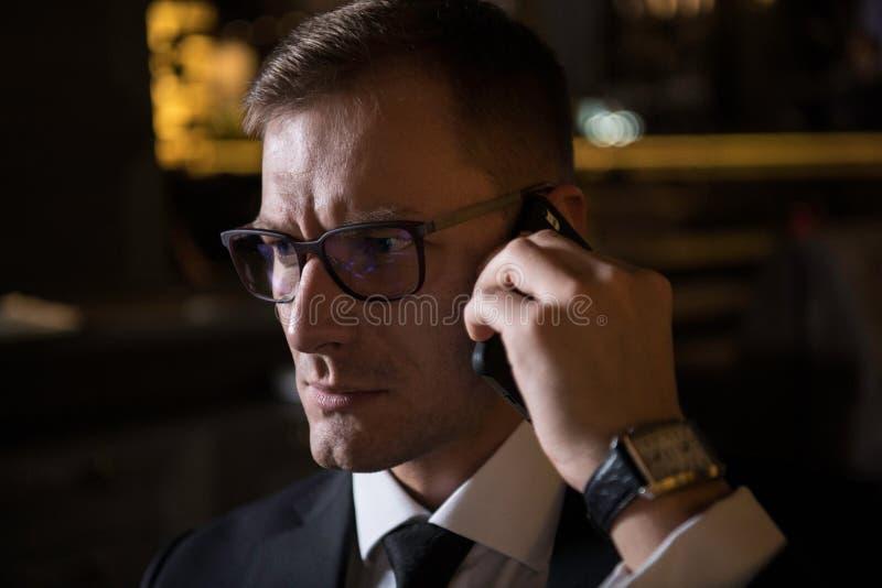 Portret van het ernstige knappe elegante Kaukasische zakenman spreken op de telefoon stock afbeelding