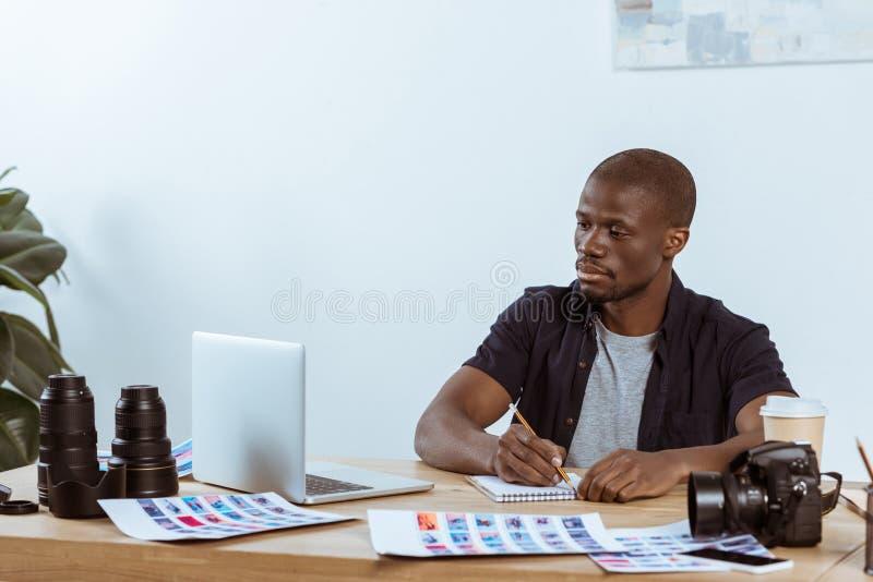 portret van het geconcentreerde Afrikaanse Amerikaanse fotograaf werken bij werkplaats met laptop stock afbeeldingen