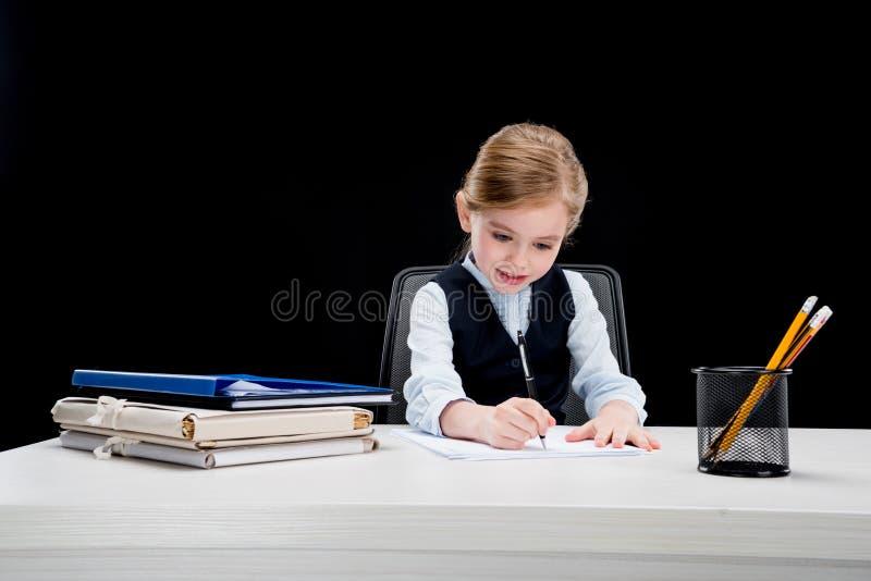 Portret van het geconcentreerde bedrijfsmeisje schrijven bij lijst royalty-vrije stock afbeelding