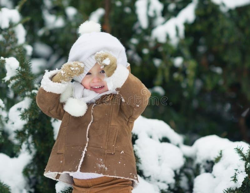 Portret van het gelukkige baby kijken uit van hoed in de winterpark royalty-vrije stock foto