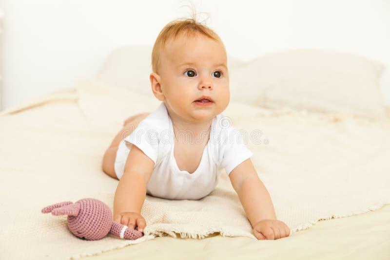 Portret van het gelukkige glimlachbaby ontspannen op het bed stock fotografie