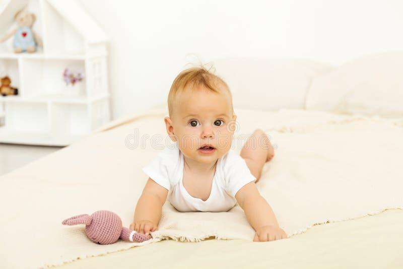Portret van het gelukkige glimlachbaby ontspannen op het bed stock foto's