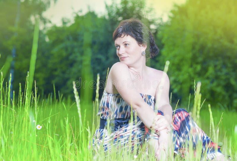 Portret van het Gelukkige het Glimlachen Kaukasische Donkerbruine Vrouw Stellen in openlucht op Aardachtergrond bij Zonsondergang royalty-vrije stock afbeeldingen