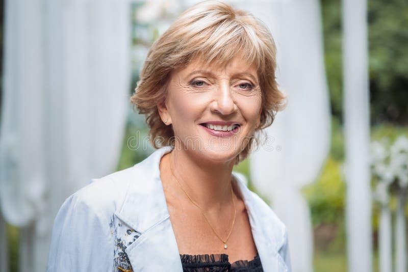 Portret van het gelukkige hogere mooie vrouw stellen in de lentepark royalty-vrije stock foto's