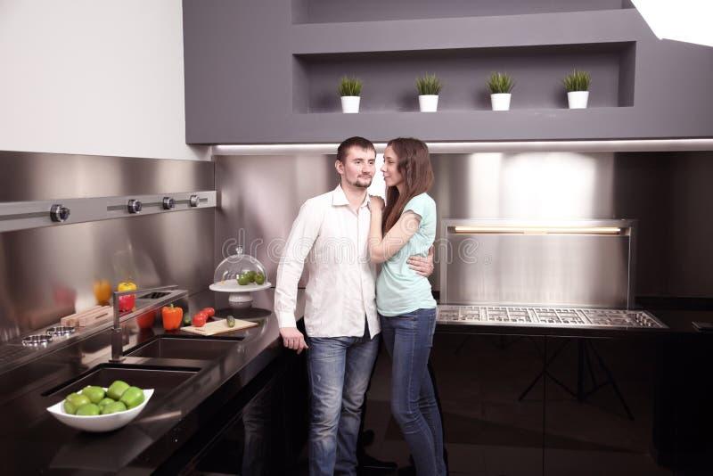 Portret van het gelukkige jonge paar koken samen in de keuken stock afbeelding