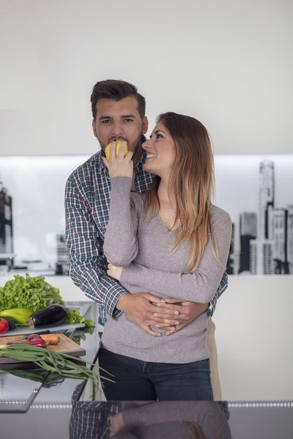 Portret van het gelukkige jonge paar koken samen in de keuken thuis royalty-vrije stock afbeelding