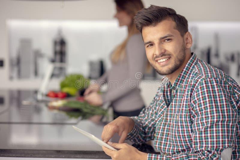 Portret van het gelukkige jonge paar koken samen in de keuken thuis stock afbeelding