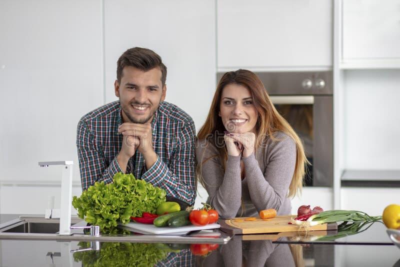 Portret van het gelukkige jonge paar koken samen in de keuken thuis royalty-vrije stock afbeeldingen