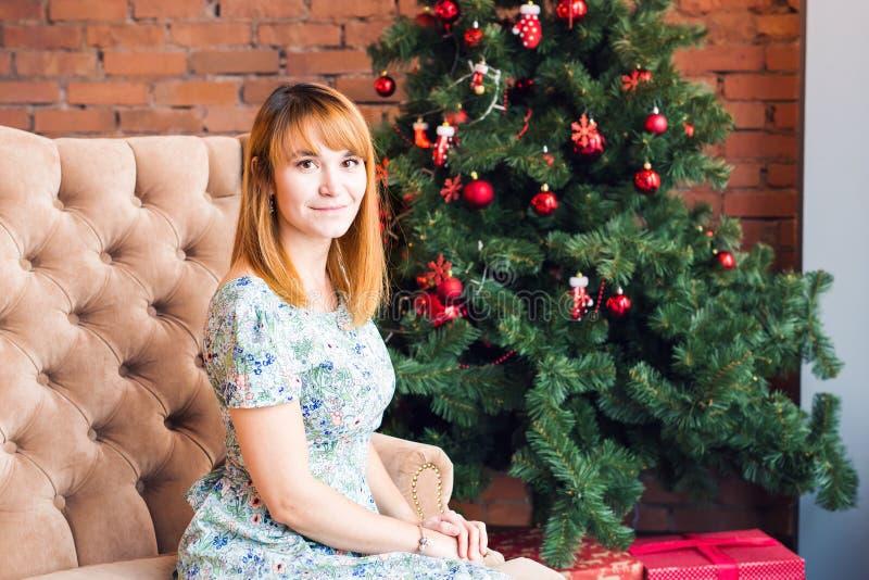Portret van het gelukkige jonge vrouw ontspannen dichtbij Kerstmisboom royalty-vrije stock afbeelding